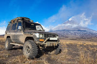 Lifted sport utility vehicle Toyota Land Cruiser Prado on background eruption active volcano. Car modified transmission for travel, off-road trip
