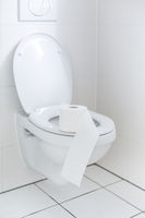 White toilet with toilet paper. Symbol for shopper panic during corona virus