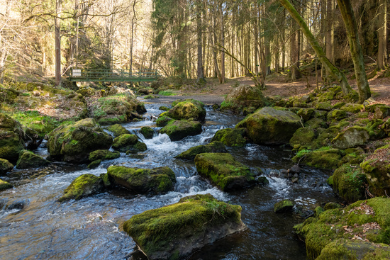 river flowing round green mossy rocks in close up
