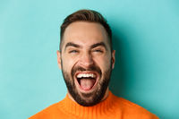 Headshot of happy and carefree man with beard, laughing and looking at camera, standing in orange sweater