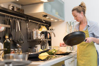Stay at home housewife woman cooking in kitchen, salting dish in a saucepan, preparing food for family dinner.