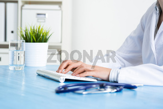 Doctor typing at computer keyboard