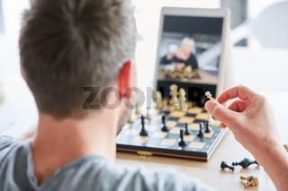 Mann hält eine Schachfigur in der Hand beim Schach