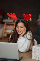 Female with antlers while speaking with online friend on laptop