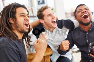 Befreundete Männer jubeln zusammen beim Fußball schauen