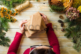 The woman packs Christmas presents from eco materials