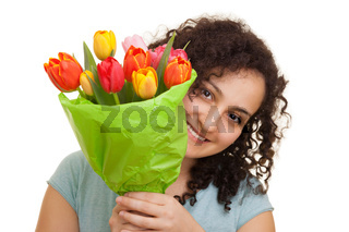 Young natural woman with curly hair looking around a bouquet of colorful tulips she is holding in front of her face, isolated on white background. Mothers day, Valentines day, Easter and surprise Concept.