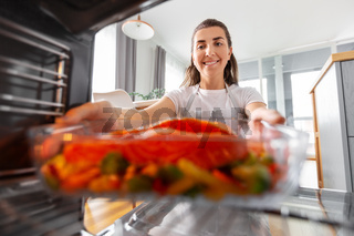 woman cooking food in oven at home kitchen