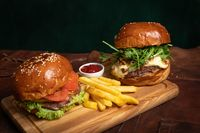 Fresh american amazing beef burgers served with french fries, one with fried walnuts and grilled cheese on a decorative wooden part of simple mechanism. Restaurant concept. Fast food, street food concept