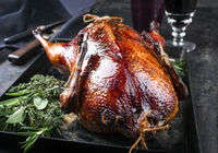 Traditional roasted stuffed Christmas Peking duck with herbs as closeup on a board
