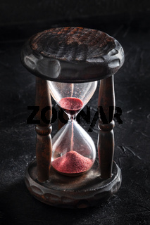 Time is running out concept. An hourglass with sand falling through, on a black background