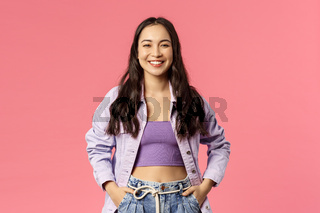 Portrait of cheerful, carefree smiling korean girl with happy pleased expression, hold hands in pockets, enjoying summer, having great plans, found excellent deal, online courses or product promo