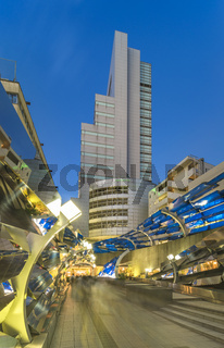 Futuristic architecture with mirroring and transparent blue plastic panels swiveling in Shibuya dist