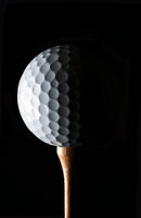 Golf Still Life. Closeup low key golf ball on wood tee with strong side light, against a black background.