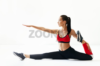 Young fitness woman stretching on white background