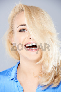 Laughing playful blond hiding behind her hair