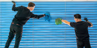 two male professional cleaners cleaning blue blinds on a large window front with micro fiber cloths