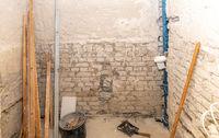 Baustelle eines Badezimmers im Rohbau mit Holzlatten, Wasserwaage, Eimer und Kehrschaufel
