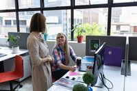 Two diverse businesswomen working in creative office