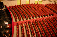 Red seats in the rows without people in Vienna State Opera auditorium.
