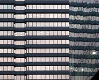 the facade of a large office urban building with rows of windows illuminated at twilight reflected in the glass facade of an office block