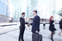 Business people shaking hands in street
