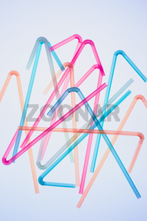 Colorful plastic straws scattered over blue background