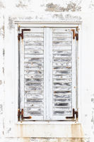 White weathered rusted wooden window shutters.