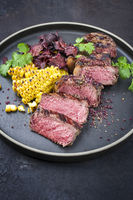 Barbecue dry aged wagyu roast beef steak with corn and vegetable chips offered as close-up on a modern design plate