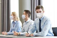 group of businesspeople in masks meeting at office