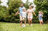 Familie und Kinder spielen Fußball im Garten
