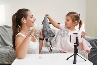 Mother with child streaming online video of unboxing clothes. Influencer occupation, mommy blog