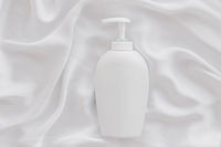 Blank label cosmetic container bottle as product mockup on white silk background