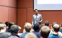 Business speaker giving a talk at business conference meeting event.