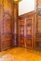 Closed elegant lumber door with engraved decorations, installed in wooden ornamental archway