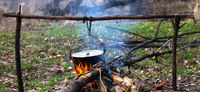 Cooking in old sooty cauldron on campfire