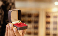 Close up, hands showing Gold Ring at jewelry box with copy space at jewellery store.
