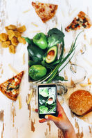 Unrecognizable woman shooting healthy vegetables near junk food