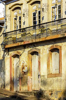 Facade of old house in colonial architecture worn by time