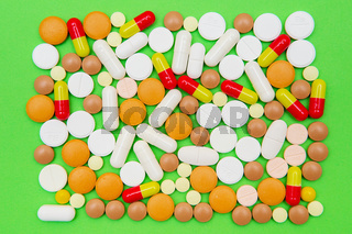 drugs capsules and pills on green background