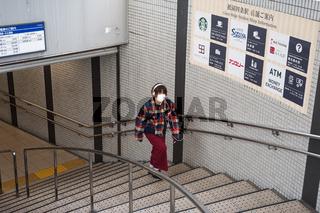 Kyoto, Japan, Frau mit Mundschutz geht Treppe einer U-Bahnstation hoch