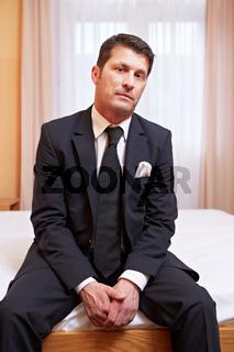 Geschäftsmann sitzt in Hotelzimmer