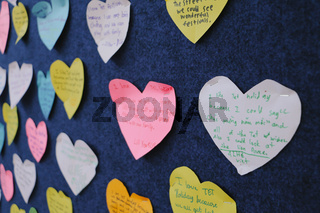 Billboard of wishes notes in heart shape close up