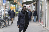 Black Man Standing on Sidewalk Listening to Earphones with Head Turned