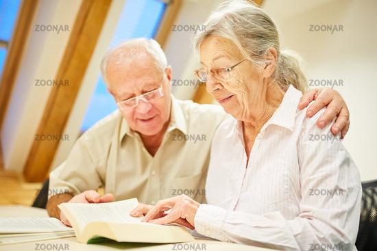 Paar Senioren mit Brille beim Buch lesen