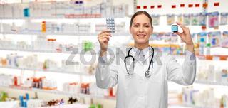 smiling female doctor holding medicine pills