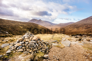 Pile of stones and footpath leading to beautiful valley in autumn colours with Mourn Mountains in background