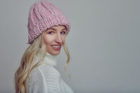 Smiling young woman in pink knitted winter hat
