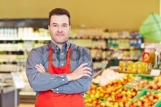 Marktleiter mit verschränkten Armen im Supermarkt