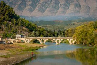 Gorica bridge over Osum river with mountain background, Berat, Albania